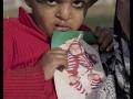 Lors d'une manifestation un enfant montre une photo de lui-même avant d'être opéré.